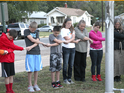 Wellington Middle School students say a prayer at 7 a.m. this morning.
