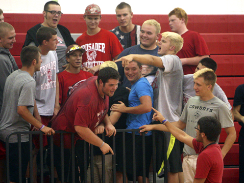 Wellington's student section, made up mostly of the football team, cheer on the volleyball girls.