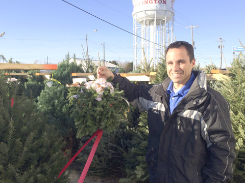 """Mill Creek General Manager Brandon Earl shows off a """"kissing"""" ball as part of the many Christmas decorative items on sale at the Wellington store."""