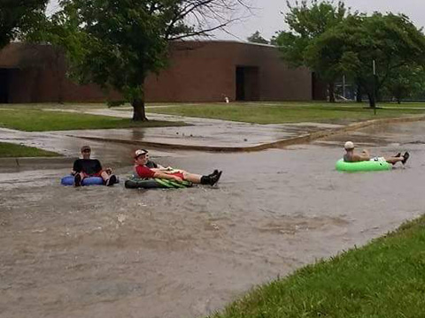 "Who needs a river to float down? These young men decide to go tubing on the ""canal"" route in west Wellington by Eisenhower Elementary School, Saturday. This pictures was taken by Rachel McGuire."