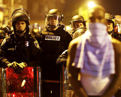 A man stands in front of a line of police officer in riot gear last week in Baltimore. (AP News photo).