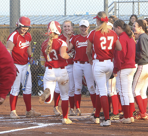 Ryleigh Buck is greeted at home after lifting Crusaders to a 2-1 lead after homer in bottom of sixth.
