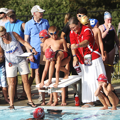 Wellington assistant swim team coach Cindy Tracy is surrounded by young Sailfish swimmers during meet with Twin Rivers.