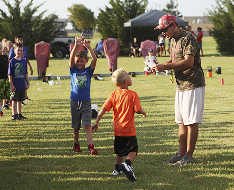 Wellington head football coach Zane Aguilar speaks to an inspired youth at the football camp Tuesday.