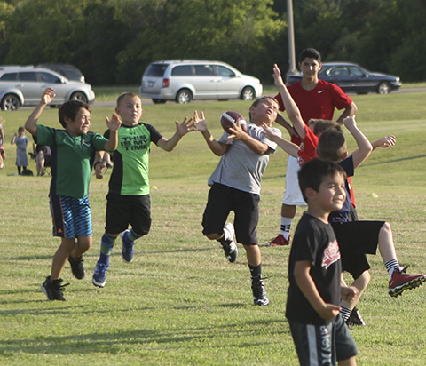 Youth football players go through passing drills.