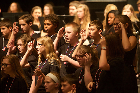 """Above: Feature speaker Jim Valentine, and After School WMS singers performing """"God Bless the U.S.A."""""""